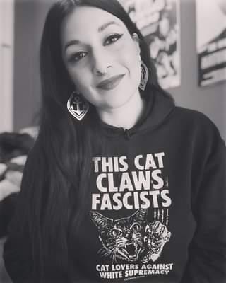 """Ist möglicherweise ein Schwarz-Weiß-Bild von eine oder mehrere Personen und Text """"THIS CAT CLAWS FASCISTS CAT LOVERS AGAINST WHITE SUPREMACY ۔MU CAMAGI"""""""